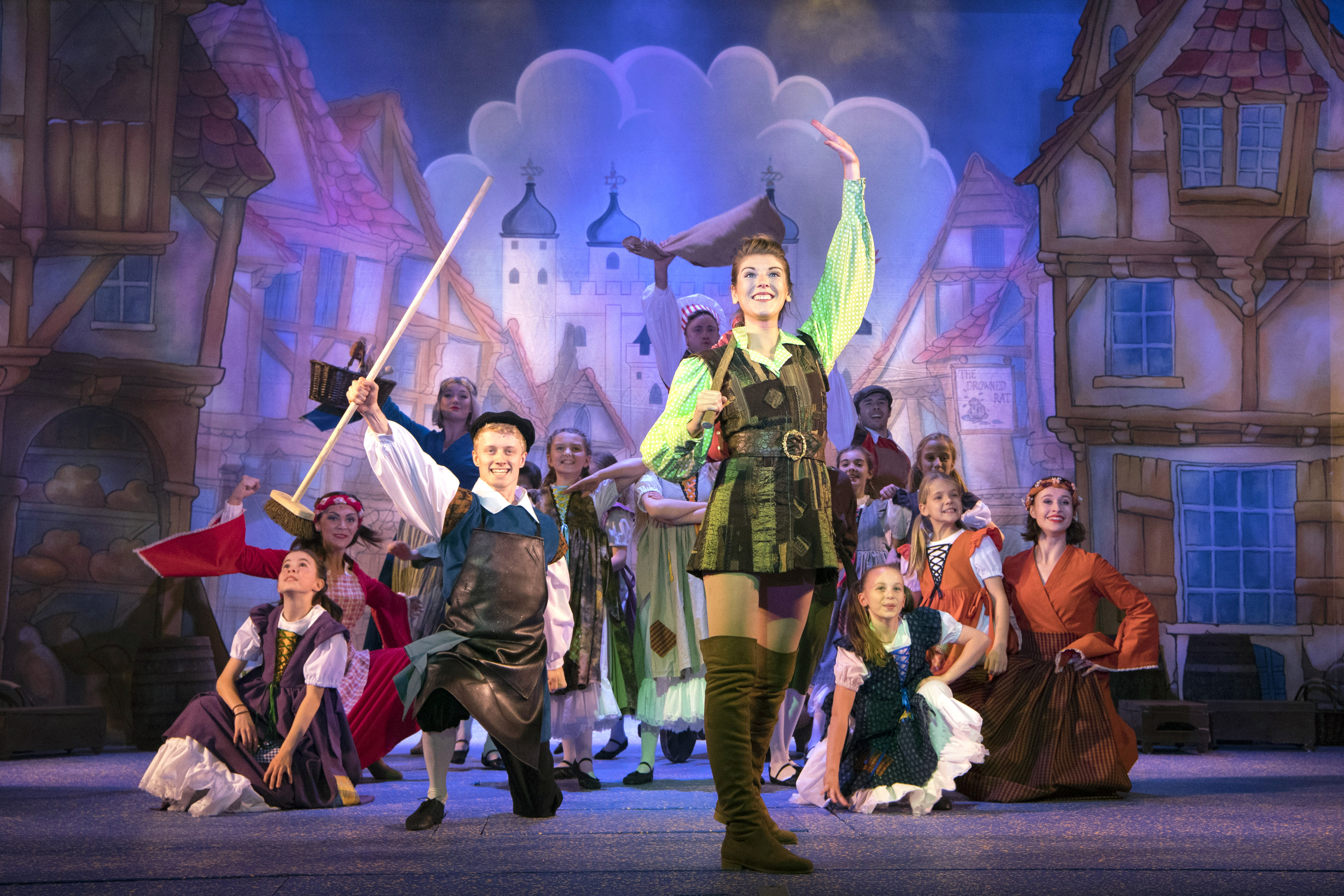 Cast of Dick Whittington - Dick Whittington holds hand up in the air