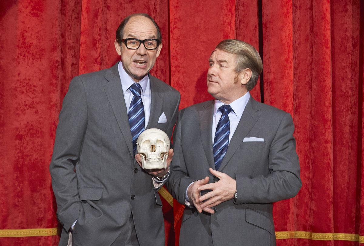A look alike Eric & Ern are on stage with a skull