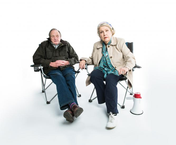 A man and woman sit in folding chairs looking at the camera.