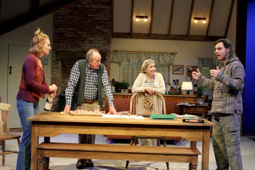 Four people stand around a wooden table.