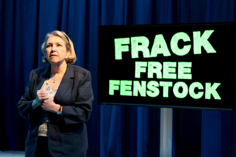 Anne Reid, in a smart jacket, speaks in front of a large sign which reads FRACK FREE FENSTOCK