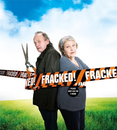 A man and a woman stand back to back behind black and orange striped tape which repeats the word FRACKED