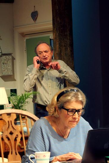 James Bolam is speaking on the telephone as he stands behind Anne Reid typing on a laptop.