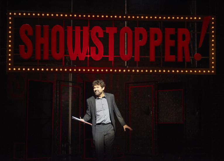 Man standing in front of Showstoppers sign