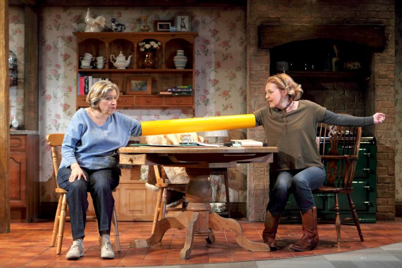 Two women sit across a table with their arms in a connecting yellow tube.
