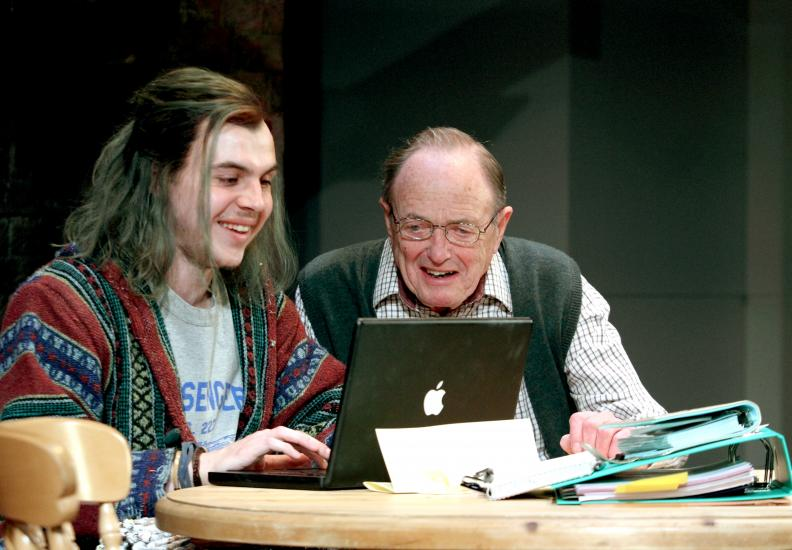 James Bolam excitedly looks over the shoulder of a happy man typing on a laptop.