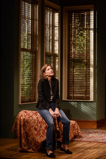 A woman (Belinda Lang) sits sadly on the edge of a chair looking up. Behind her is the large window of what appears to be a grand living room.