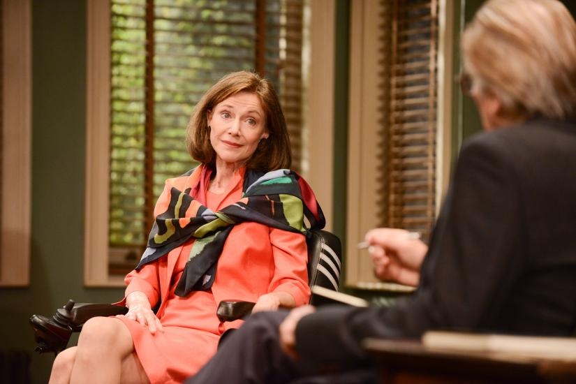 A woman (Belinda Lang) is in discussion with a man. They are seated and the woman looks tired and a little sad.