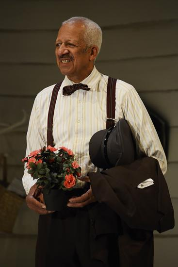 A man holds a pot of flowers and smiles