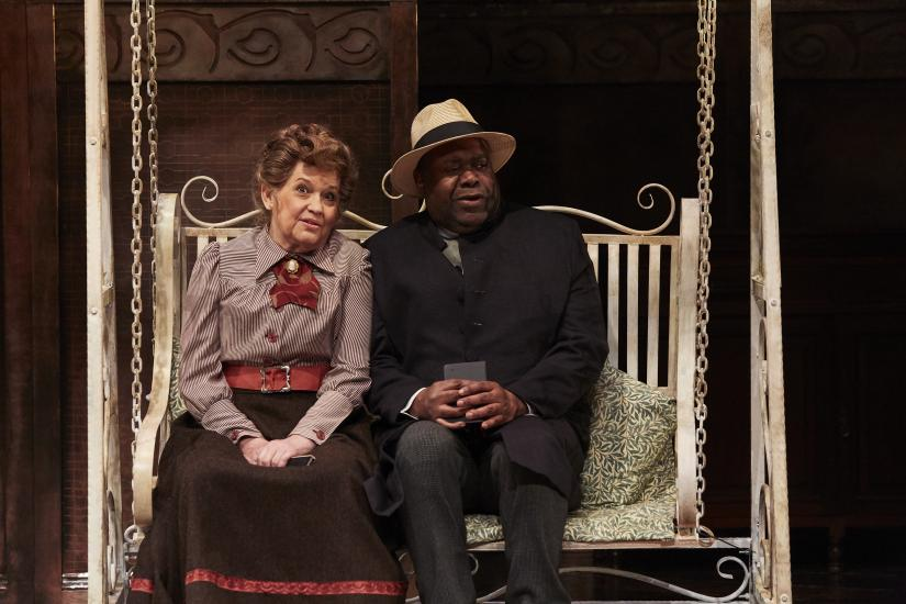 A man and a woman sit on a garden seat