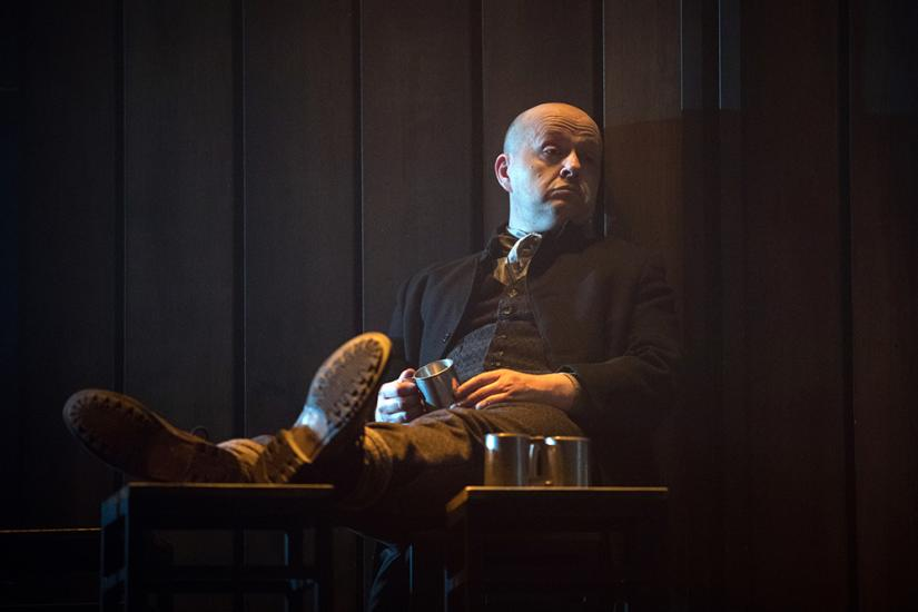 A bald man sits with his legs out in front of him