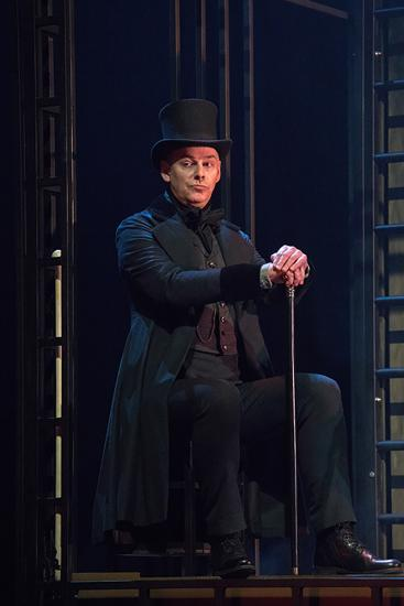 A man in a black coat and top hat sits with a cane.