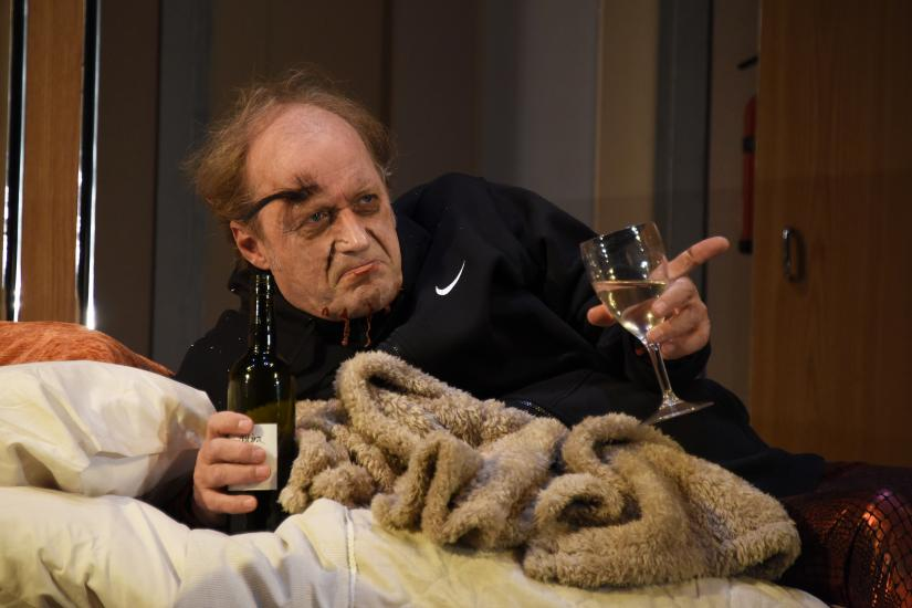 A man lies on a bed with a drink