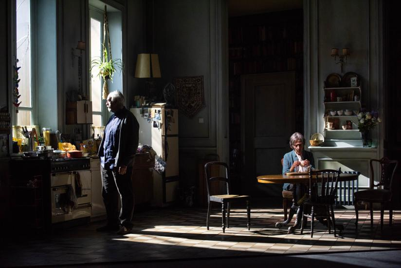A man and woman stand in the shadows in a kitchen