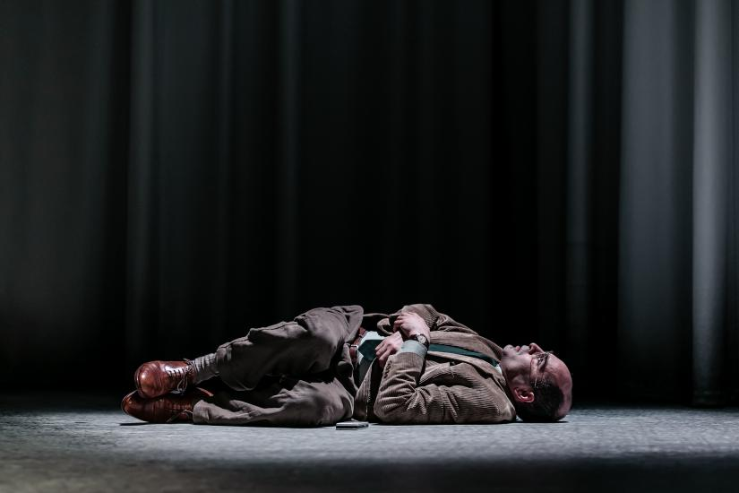 A man lies on the floor in a suit