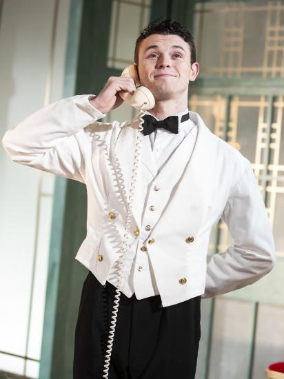 A waiter is smiling on the telephone