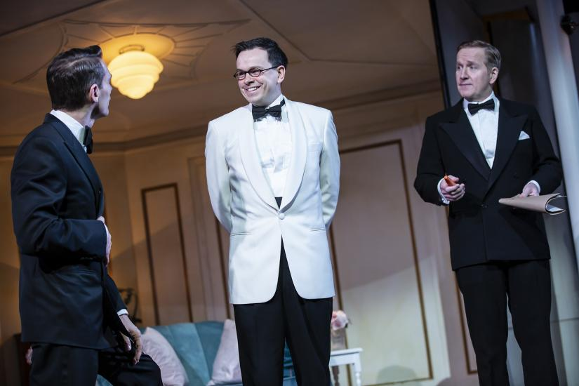 Three men in evening wear are stood talking