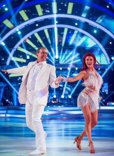 Strictly Come Dancing dance shot of Rev Richard Coles in a white suit and his partner