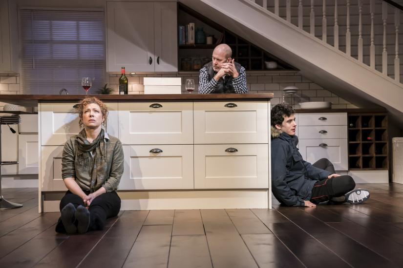 A man, woman and teenage boy sit around a kitchen staring intensely