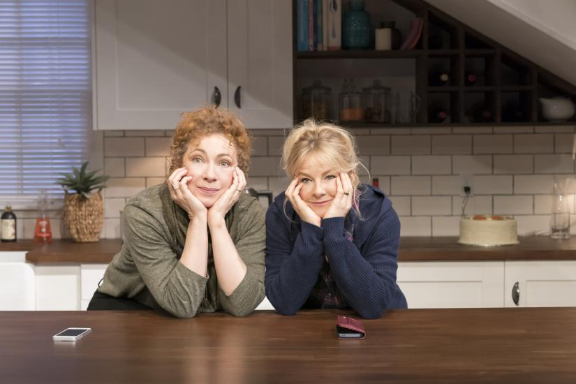 Two women lean on a kitchen counter smiling