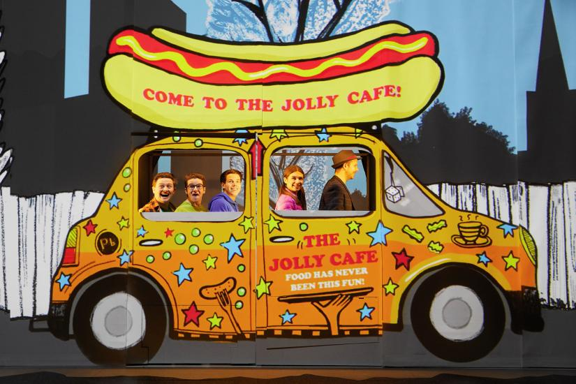 a group of people are in a food van with a hotdog on the top