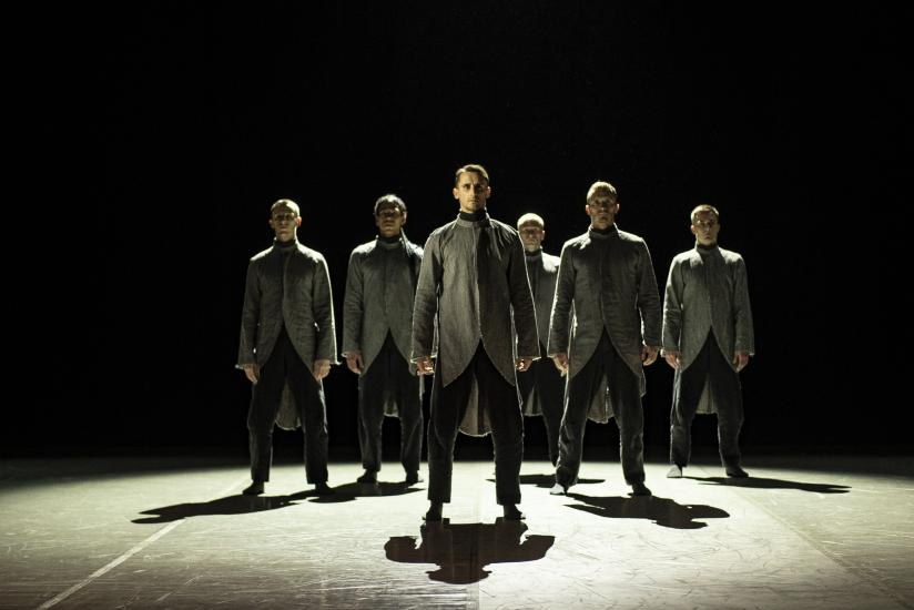 A group of male ballet dancers stand in formation