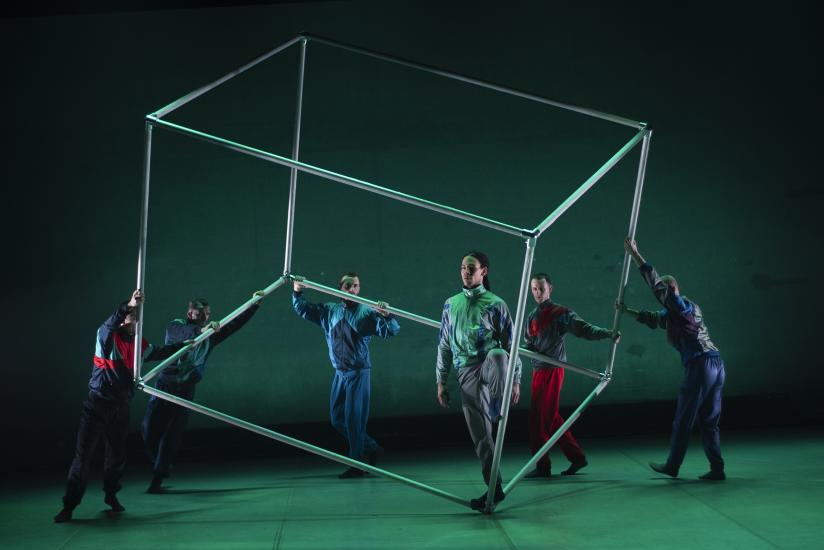 A group of male ballet dancers with a big metal cube