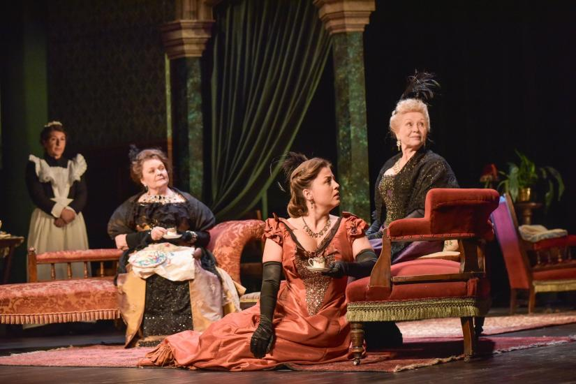 4 women sit in a grand drawing room