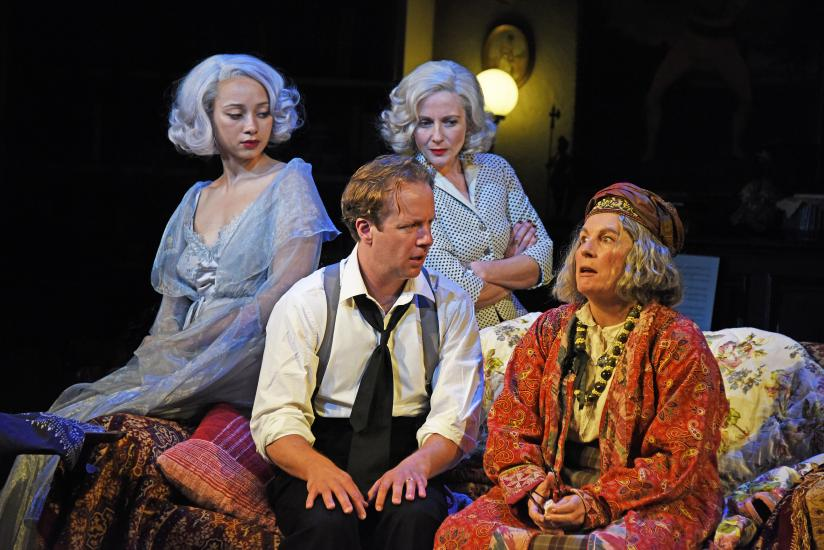 A man and a clairvoyant sit together, whilst his wife and ghost of his ex-wife watch