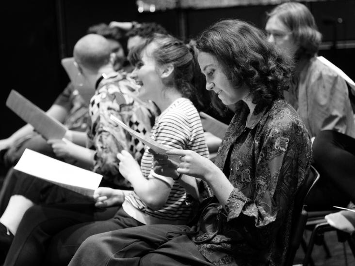 Members of the cast look intently at their scripts.