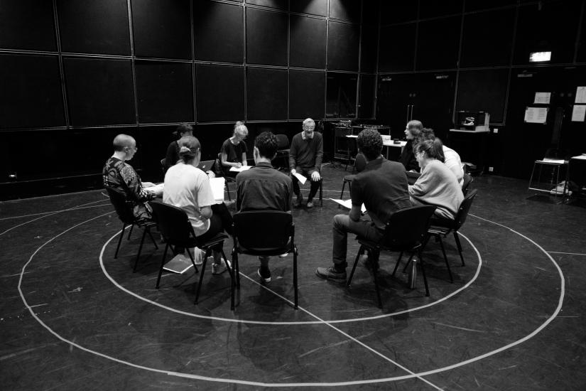 An image showing the full cast and creative team in a close, seated circle.