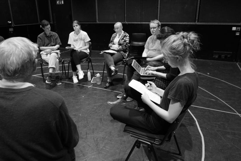 The cast and crew rehearse the reading in a circle.