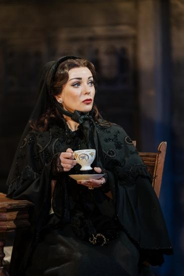 a woman dress in black Victorian clothes has a cup of tea