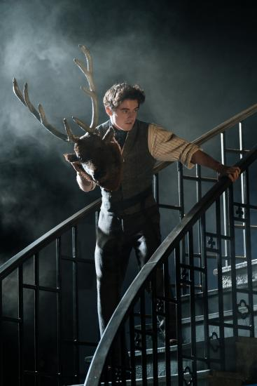 a man stands on a staircase holding a stags head
