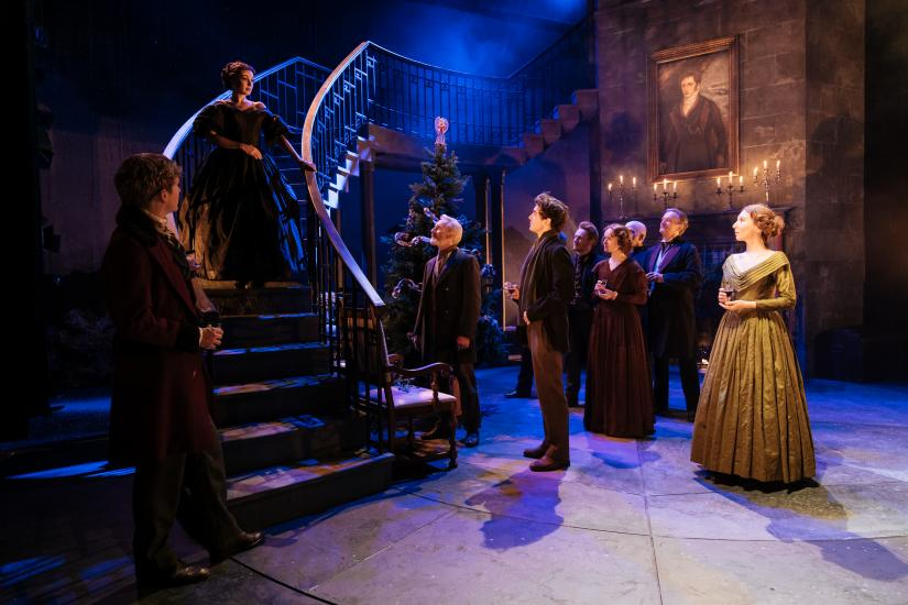 The cast stand looking up at a man on metal stairs