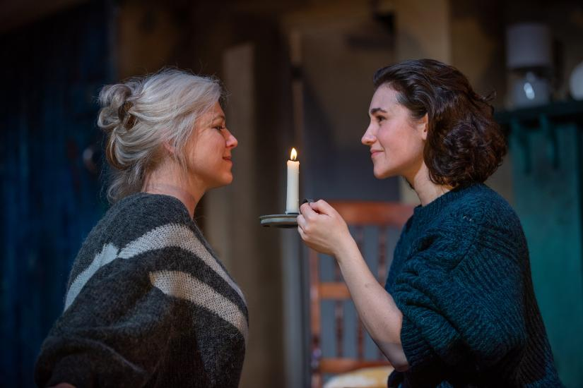 Two women look at each other holding a candle between them