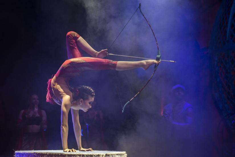 An acrobat balances with legs outstreched