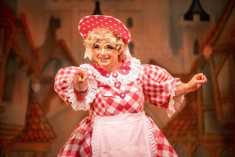 Dame Trott wears a pink gingham dress and matching hat, pointing to the audience
