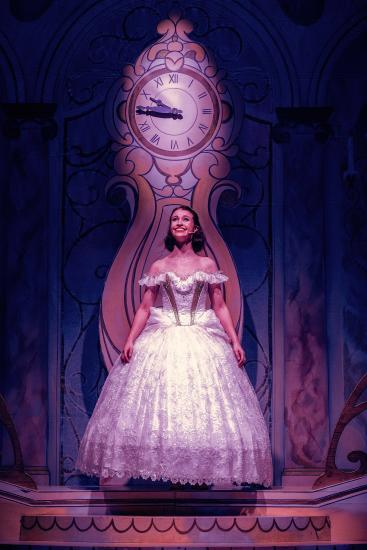 Cinderella wears a beautiful ball gown, and stands infront of a large clock