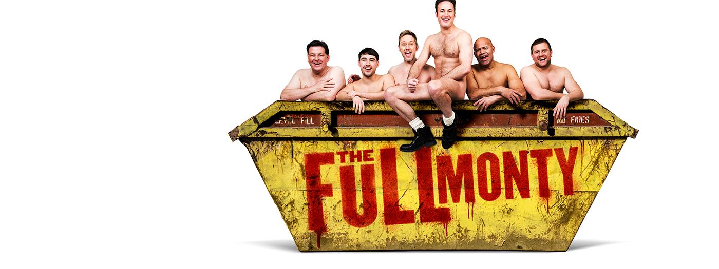 Six men sit naked in a skip with The Full Monty spray painted on the side
