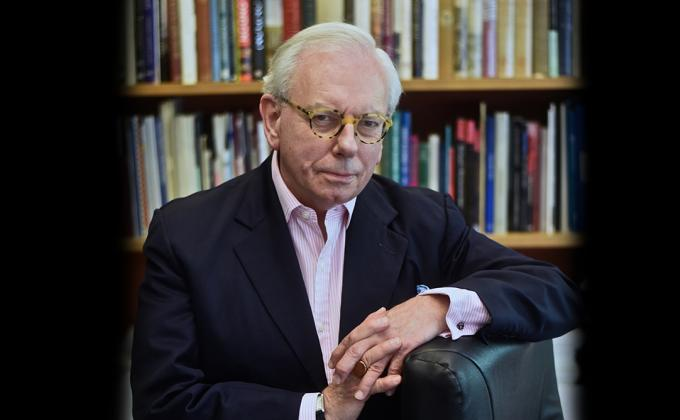 David Starkey sitting with arms crossed by books