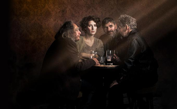 3 men and 1 woman sit round a table in a pub with drinks, she looks wistful