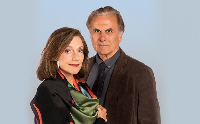 Belinda Lang and Oliver Cotton stand against a blue background