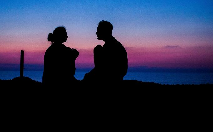 A silhouette of a man and woman on a beach at dusk