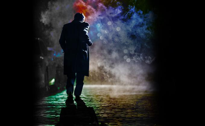 A man walks on cobbles in a smoky street, its shadowy
