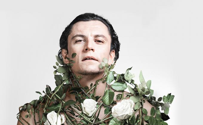 A man looks ahead at the camera, covered with roses and rose thorns
