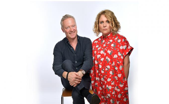 Rory Bremner laughs, sitting on chair, with Jan Ravens in a red dress looking a bit more serious