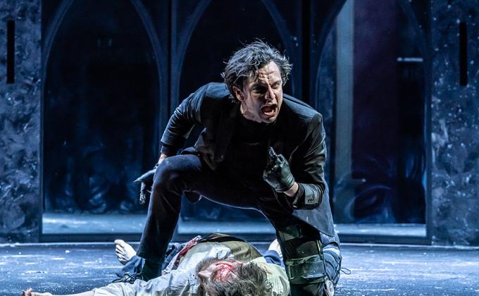 Richard III leans over a lifeless body, he is angry and points at himself