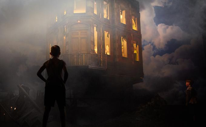 A boy stands in a smokey atmosphere looking at a lit up home