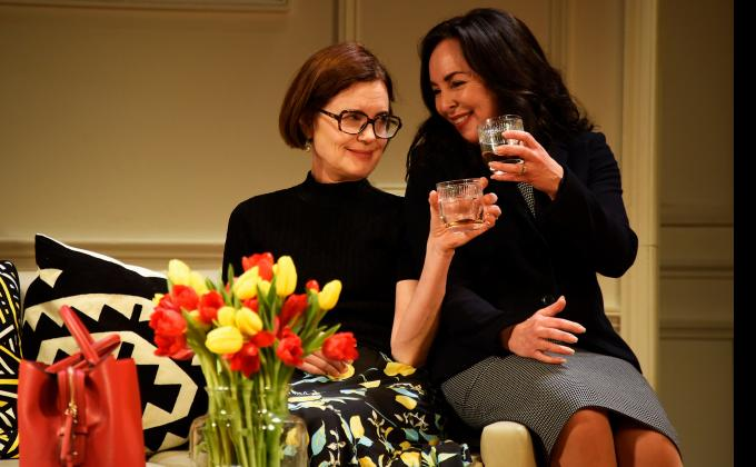 Two woman clink glasses and smile